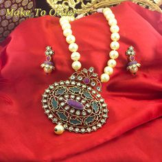 A beautiful Ethnic Necklace Set with White colored pearls mala and drop hangings. Also it has beautifull minakari on the penant and has Kundan Stones Studded on top of the pendant.