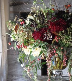 Amy Merrick. Dahlias, pepperberries, grasses, rose hips and brunia look wild and beautiful in a clear glass vase.