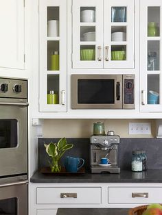 white kitchen with glass front cabinets, black honed granite countertops
