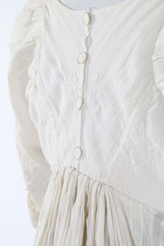 Lot 119 : A whitework embroidered empire-line muslin dress, circa 1805. A whitework embroidered empire-line muslin dress, circa 1805. with woven self-stripes and vertically embroidered foliate bands, nice back detailing with four Dorset buttons, slightly trained hem, bodice with internal linen narrow front closure flaps and remains of triangular front bodice panels. - See more at: http://kerrytaylorauctions.com/one-item/?id=119&auctionid=402#sthash.r9Sd3X5S.dpuf