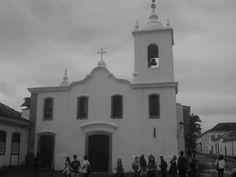 A imagem mostra a fachada da Igreja de Nossa Senhora das Dores. Revelando o que tem na construção, as janelas, o sino, a cruz, porém todos em uma única imagem.