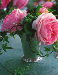 A silver mint julep cup holds three glorious roses, variegated ivy and immature blueberries. Elegant yet easy to arrange!