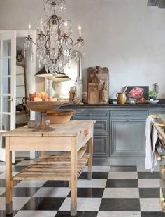 The kitchen floor is checkered tiles of Belgian stone and white marble.  The sink is antique. A charming antique counter, crystal chandelier and French Delaubrac stove. The cabinets are painted a warm shade of gray blue.