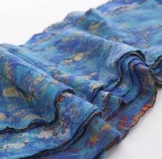 The Red Sari: Turquoise and cobalt blue wool fibers are fused with a vintage silk sari to create a one-of-a-kind work of wearable art. Handmade in Nepal. Price: $70.00