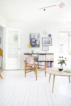 Un intérieur danois frais, aux couleurs d'été. Fauteuil, table basse. Mur et sol blanc.