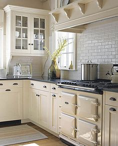Vermont Farmhouse : creamy cabinets, corbels & shelving with black countertop & pulls