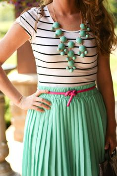 striped black and white comfy tee tucked into a teal skirt with a pink ribbon topped with a teal necklace