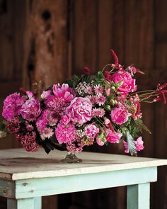 """During the growing season, Benzakein offers several flower-arranging workshops at the farm. Students are given access to cut whatever blooms they want from the fields: """"We try to think of the farm as a living classroom,"""" she says. Here, she has combined garden roses, peonies, astrantia, sweet peas, ninebark, copper beech, and Sanguisorba in varying shades of red and pink for an exuberant, romantic arrangement."""