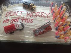Toy Fire Trucks Ready to Assist With Putting Out the Candles on a Forty Year-Old's Birthday Cake