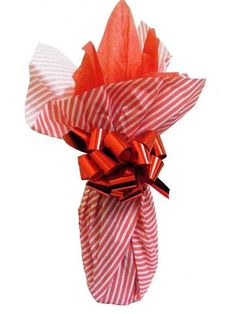 wine bottle wrapped in dizzy diagonals red patterned tissue paper, red plain tissue paper and tied with a metallic stop & lock bow all available at The Wrapping Ranch