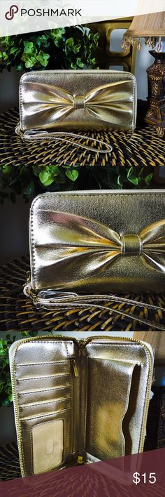 """Gold Bow Cell Phone Case Wallet Large Fun and feminine, the Women's Large Bow Cell Phone Case Wallet by Mossimo Supply Co.™ is so versatile because it can be used as a wallet, a wristlet or and adorable clutch. Sporting a removable wrist strap, this roomy wallet packs a lot into a sleek package, including 5 card slots, an ID pocket, a slip pocket, and a cell phone pocket. Vegan leather Dimensions: 7.5 """"H x 4 """"W x 7.5 """"D Fits my iPhone 6. ⭐️THIS WALLET IS AWEOME!⭐️ Mossimo Supply Co Bags…"""