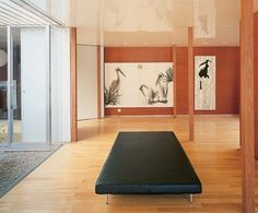 """In the living area are paintings by the client's daughter. The walls are stained wood veneer; the floors are birch. """"Wood is part of Japanese culture,"""" Nishizawa notes. Ryue Nishizawa, Weekend House, Japan Photo, Image House, Architectural Digest, Japanese Culture, Wood Veneer, Floor Chair, Living Area"""