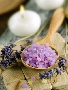 Spoonful of lavender bath salt and aromatic lavender flowers - spa body care products.