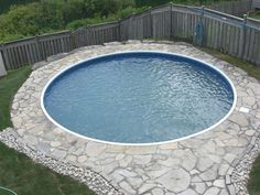 Unique Round Semi Inground Pool Small Grovel Wood Fence Stoned Deck