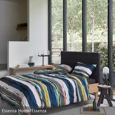 Für eine frische Atmosphäre im Schlafzimmer sorgt die lebendige, gestreifte Bettwäsche. Die restliche, neutral gehaltene Einrichtung rückt die Bettwäsche…