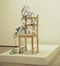 Wire art by David Oliveira, it looks like a line drawing or sketch. It's doing something strange to my eyes but I like it. Even his signature is in wire near the bottom right of the chair.
