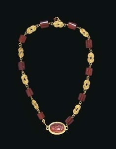 A ROMAN GOLD AND CARNELIAN NECKLACE  CIRCA 2ND CENTURY A.D.  Composed of ten faceted carnelian beads, each threaded by a plain wire looped at each end and joined to elaborate links in the form of Herakles knots, one with a crescent pendant at the center with a small carnelian bead, one end terminating in a hook, the other end joined to an oval box bezel, set with a convex carnelian ring stone engraved with a lion walking to the left on a groundline