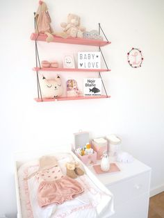 Une étagère rose au-dessus d'une commode à langer