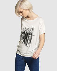 Camiseta oversize en color blanco con print delantero en negro. Tiene manga corta y escote redondo.