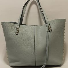 """Rebecca Minkoff Unlined Tote Bag Rebecca Minkoff Unlined Tote Bag 100% Authentic   Color: Pale Sage / Light Gold Style: HR25IULT32 Retail: $275.00  Lose the baggage: In unlined leather, Rebecca Minkoff's supple leather shopper houses all your daily essentials without weighing you down. Subtle studs and center seaming make for a chic finish. Double handles Magnetic snap tab closure; unlined Includes detachable coin purse with zip closure 18.5""""L x 5""""W x 11""""H; 9"""" handle drop Leather Imported…"""