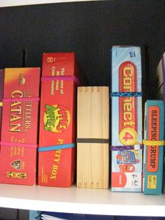 """A Simple Tip for Tidy Board Game Storage """"Inexpensive headbands. They are just the right size elastic to wrap around the average board game box so that you can stand them up in a closet without fear of lids coming loose. Board Game Organization, Board Game Storage, Storage Organization, Storage Ideas, Safe Storage, Book Storage, Storage Boxes, Board Game Box, Board Games"""