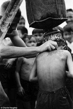 A medic gives Vietnamese children a shower using a Lyster Bag
