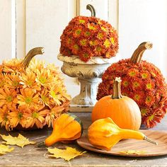 Flowered Pumpkins - Create this beautiful floral display using yellow and orange mums. Cut the heads from the flowers and hot-glue them all over the pumpkins. Display on tabletops or in small footed urns.