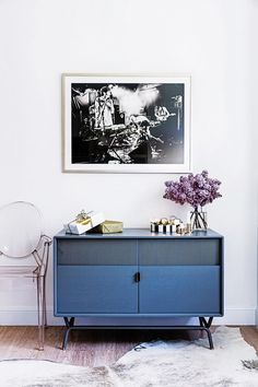 Chic living space with a blue dresser, an acrylic chair and graphic art