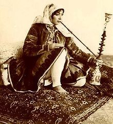 Persian woman, in Qajar era dress seen here smoking the traditional Qalyan