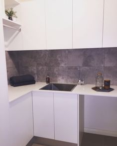 Laundry styling. White cupboards, white stone benchtops and grey travertine large tile splashback. NSW, Australia.