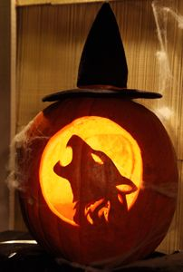 Elaborately carved halloween pumpkin of a howling dog