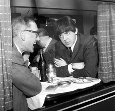 """Paul McCartney of The Beatles and actor Wilfred Bramble chat at dining table on the train to South Molton, Devon in the special train for the filming of """"A Hard Day's Night"""" 5 March 1964."""
