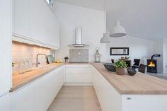 aménagement cuisine en U blanche et moderne avec des plans de travail en bois clair
