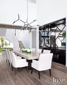 One of New York artist Lindsey Adelman's articulated chandeliers crowns the dining room, creating an  industrial counterpoint to the more glamorous black lacquered bar. An oak-and-goatskin dining table by Ekena adds a sumptuous layer to the diverse materials palette and centers slipcovered Artefacto chairs.
