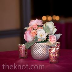 Cocktail table centerpiece with pink, peach and white roses and sweetheart roses with green gray leaves surrounded by mercury glass votives