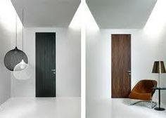 Hoge houten deuren zonder kozijn in een strak gestucte wand geeft een rustige en serene uitstraling