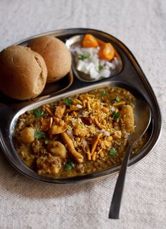 misal pav recipe - a popular mumbai street food of usal (sprouts curry) topped with onions, tomatoes, farsan (fried savory mixture), lemon juice and served with pav.