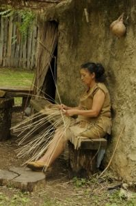 A Cherokee basket weaver works in front of a traditional house in the ancient village of the Cherokee Heritage Center in Tahlequah.  Guests can take a guided tour through the village and learn about tribal life prior to relocation.