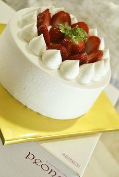딸기 생크림 케이크. White cake with whipped cream frosting topped with fresh strawberries coated with a glaze