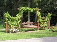 Качели в саду. Зелень в декоре качелей. Цветы.