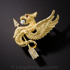 Antique Griffin and Diamond Arrow Pin. This fierce, ruby-eyed, mythological creature, half eagle, half lion - griffin (or gryphon) by name - is taking a wild ride on a diamond-set arrow to deliver a sparkling diamond in his beak via air mail. Masterfully sculpted in gleaming 18K yellow gold - circa 1900.