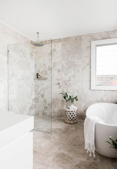 Hardwearing limestone has been used in this bathroom. Large-format tiles mean less grout to scrub, while a freestanding bath tub provides a focal point in the room. Photography: Maree Homer | Styling: Kayla Gex | Story: Australian House & Garden