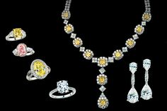 From left: 3ct Fancy Intense Yellow Cushion with shield cut sides, 4ct Fancy Pink oval with pave and modified bullets, 4ct Fancy Yellow oval in a micro-pave ring, cushion cut ring, Fancy Intense Yellow and White Asscher necklace with detachable drop, 45ct total, Pear-shape dangle earrings, 6ct total.