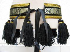 Siguiendo con el estilo tribal, ahora os muestro un cinturón, combinando negro y dorado, con una cenefa de elefantes al estilo hindú. Es muy sencillo, pero tiene un brillo muy bonito y los flecos se mueven mucho al bailar.  Espero que os guste…