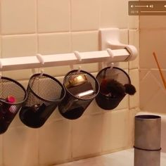 Use pencil holders and shower curtain hooksto turn an oddly placed towel rack into a handy makeup organizer.