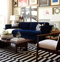 blue velvet sofa and b stripe rug and picture wall