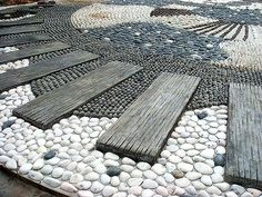 Reflexology path detail of pebble stones and wood planks at the Lokasi Port Dickson Wellness Zone in Malaysia.