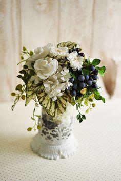 白と紫がガラスの花器から透けて見える爽やかな印象のプリザーブドフラワー&アートグリーンのアレンジメントです。 ブルーベリーの紫が清々しい白いローズやスカビオサとのコントラストでとてもきれいです。