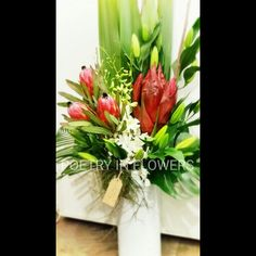 Tall corporate flowers vase arrangement. White orchids, gymea lilly, protea, oriental lillies, Reds & whites.