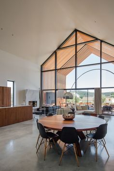 In this modern house, a large round wood dining table is surrounded by black chairs that tie in with the black window frames. #ModernDiningRoom #WoodDiningTable #RoundDiningTable #Windows